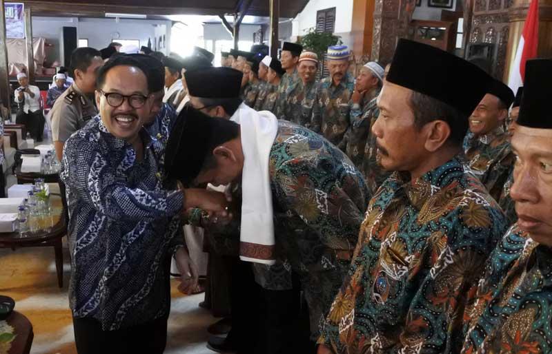 Budi Fatahillah Mansyur juga dikalungi kain surban oleh Jarianto dalam acara pelepasan CJH Tulungagung 2018 di Pendopo Kongas Arum Kusumaning Bongso, Rabu (25/7).