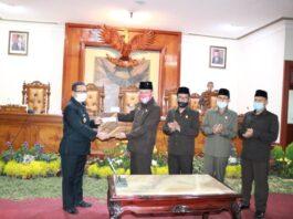 Marsono menyerahan berita acara persetujuan penetapan Perda APBD Tahun Anggaran 2021 pada Bupati Maryoto Birowo didampingi pimpinan dewan lainnya, Sabtu (28/11).
