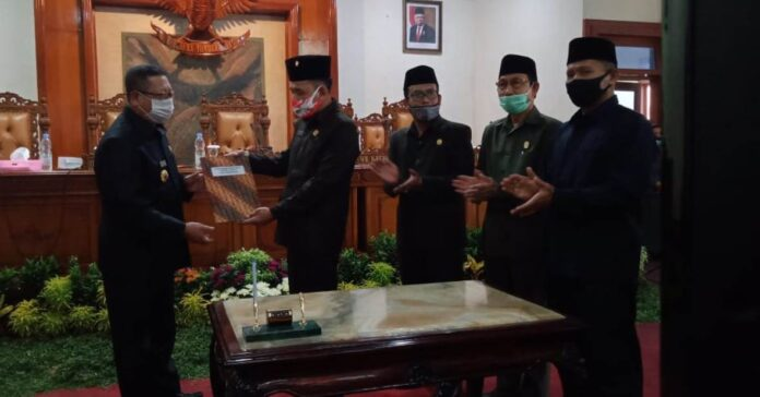 Marsono menyerahkan berita acara penetapan Perda Perubahan APBD Tahun Anggaran 2020 pada Bupati Tulungagung, Maryoto Birowo,didampingi para Wakil Ketua DPRD Tulungagung, Selasa (8/9).
